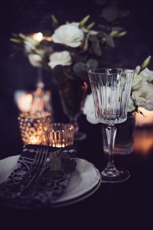 Luxury festlich gedeckten Tisch mit Kerzen, Blumen, Gläser und Besteck. Tischdekoration für ein romantisches Abendessen.