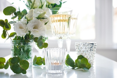 Glasses of champagne and candles: Two glasses of champagne and white flowers, candles on white table. Festive summer party decor. Kho ảnh