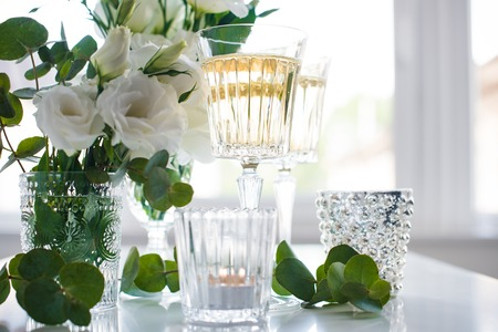 crystal glass: Two glasses of champagne and white flowers, candles on white table.