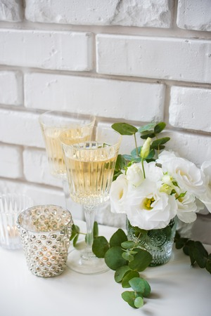 Glasses of champagne and candles: Two vintage glasses of champagne and white flowers, candles on white table by the brick wall background. Festive summer home party decor.
