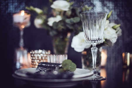 candle light dinner: Luxury festive table setting with candles, flowers, glasses and cutlery. Table decoration for romantic dinner.
