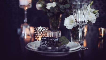 Luxury festive table setting with candles, flowers, glasses and cutlery. Table decoration for romantic dinner.