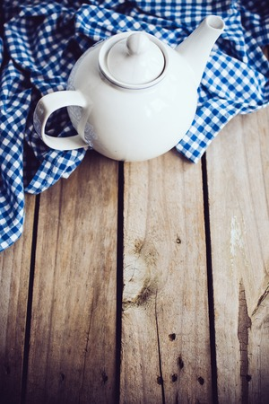 country kitchen: Large white porcelain teapot and a blue linen napkin on old wooden board, rustic kitchen background.