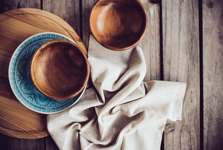 bowls: Rustic tableware, wooden bowls and ceramic plates with a linen cloth on an old vintage board. Stock Photo