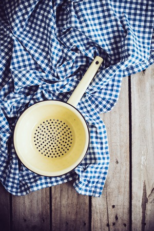 country kitchen: Yellow enamel colander and blue linen cloth on an old wooden board, rustic kitchen background.