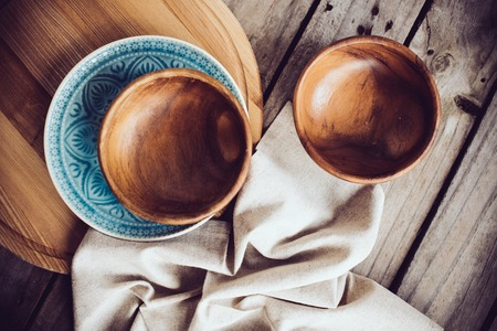linens: Rustic tableware, wooden bowls and ceramic plates with a linen cloth on an old vintage board. Stock Photo