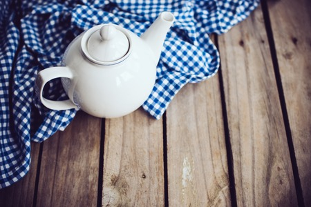 blue white kitchen: Large white porcelain teapot and a blue linen napkin on old wooden board, rustic kitchen background.