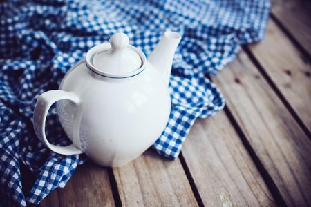 cocina antigua: Gran blanco tetera de porcelana y una servilleta de lino azul sobre tabla de madera vieja, fondo rústico cocina.