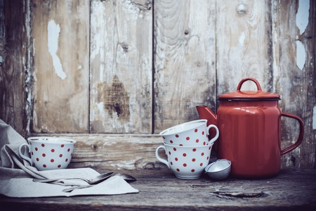 country kitchen: Vintage kitchen decor, red enamel coffee pot and cups with polka dots on an old wooden board background with copy space. Rustic home decor.