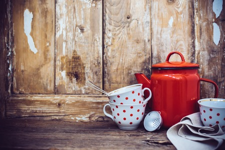 pottery: Vintage kitchen decor, red enamel coffee pot and cups with polka dots on an old wooden board background with copy space. Rustic home decor.
