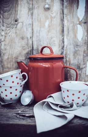 vintage kitchen: Vintage kitchen decor, red enamel coffee pot and cups with polka dots on an old wooden board background with copy space. Rustic home decor.