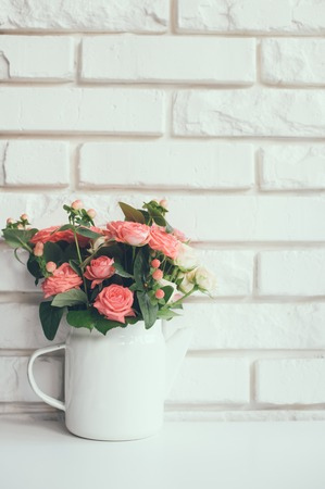 coffee pot: Bouquet of pink roses in vintage enamel coffee pot on a background of white brick wall Stock Photo