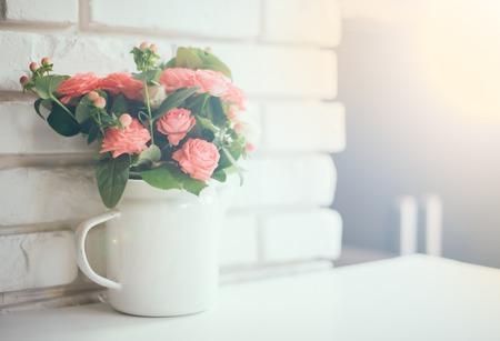 ヴィンテージ エナメル コーヒー ポット レンズで白いレンガの壁の背景のピンクのバラの花束はフレアし、スペースをコピー