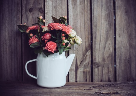 Bouquet of pink and beige roses in vintage enamel coffee pot on old wooden barn board background. Rustic flowers with copy space.