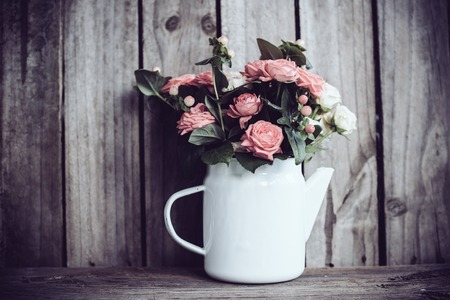 pink flowers: Bouquet of pink and beige roses in vintage enamel coffee pot on old wooden barn board background. Rustic flowers with copy space.