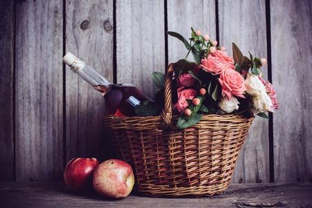 vida natural: Aún vida rústica, frescas rosas de color rosa natural y una botella de vino se levantó con las nectarinas en una cesta de mimbre en un viejo fondo de madera granero. Flores y frutas para la boda de la vendimia con copia espacio.