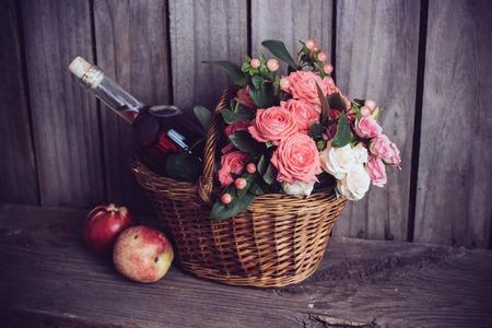 vida natural: Aún vida rústica, frescas rosas de color rosa natural y una botella de vino se levantó con las nectarinas en una cesta de mimbre en un viejo fondo de madera granero. Flores y frutas para la boda de la vendimia.