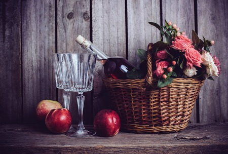 Rustic martwa natura, świeże róże naturalne różowe w wiklinowym koszu i butelką wina wzrosła w dwa kieliszki i nektarynek na starym drewnianym pokładzie stodoła tle. Kwiaty i owoce dla rocznika ślubu.