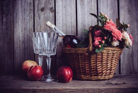 Vita rustica ancora, freschi rosa naturale rose in un cesto di vimini e una bottiglia di vino rosato con due bicchieri di vino e nettarine su un vecchio legno bordo fienile sfondo. Fiori e frutti di vintage.