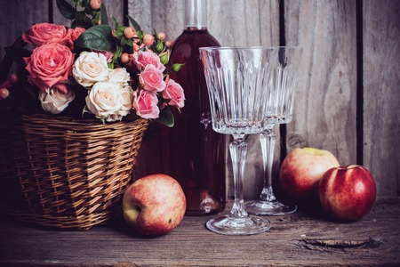 barns: Rustic still life, fresh natural pink roses in a wicker basket  and a bottle of rose wine with two wineglasses and nectarines on an old wooden barn board background. Flowers and fruits for vintage wedding. Stock Photo