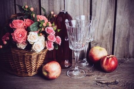 rose bouquet: Rustic still life, fresh natural pink roses in a wicker basket  and a bottle of rose wine with two wineglasses and nectarines on an old wooden barn board background. Flowers and fruits for vintage wedding. Stock Photo