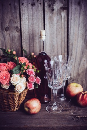 Rustic still life, fresh natural pink roses in a wicker basket  and a bottle of rose wine with two wineglasses and nectarines on an old wooden barn board background. Flowers and fruits for vintage wedding with copy space.