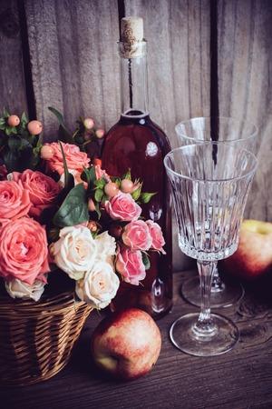 vida natural: La vida rústica todavía, frescas rosas rosadas naturales en una cesta de mimbre y una botella de vino rosado con dos copas de vino y nectarinas en un viejo fondo de madera granero. Flores y frutas para la boda de la vendimia.