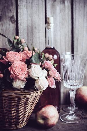 vida natural: Todavía vida rústica, frescas rosas de color rosa naturales en una cesta de mimbre y una botella de vino rosado con dos copas y las nectarinas en un viejo fondo de madera tarjeta del granero. Flores y frutos para la boda de la vendimia con el espacio de la copia.