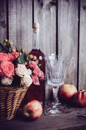 vida natural: La vida rústica todavía, frescas rosas rosadas naturales en una cesta de mimbre y una botella de vino rosado con dos copas de vino y nectarinas en un viejo fondo de madera granero. Flores y frutas para la boda de la vendimia con copia espacio. Foto de archivo
