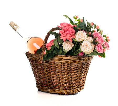in the basket: Fresh natural pink roses in a wicker basket  and a bottle of rose wine on white background isolated. Fruits, wine and flowers.