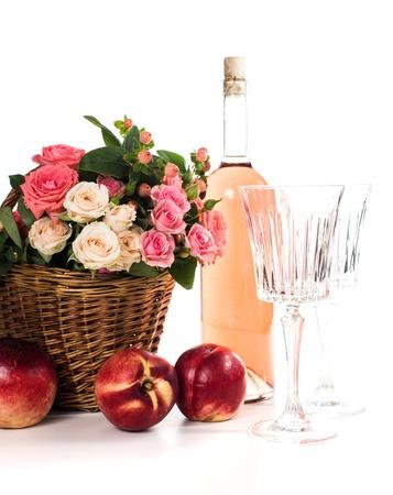 bouteille de vin: Fraîches roses roses naturelle dans un panier en osier et une bouteille de vin rosé avec deux verres de vin et de nectarines sur fond blanc isolé. Fruits, du vin et des fleurs.
