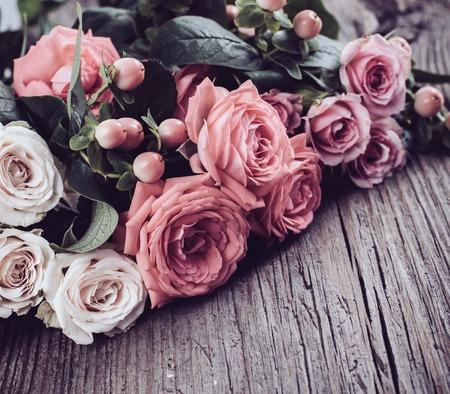 新鮮な自然のピンクとベージュ バラ古いヴィンテージの木製基板のクローズ アップ