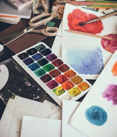 artistas: Lío en el estudio, las pinturas de acuarela, pinceles del artista y bocetos, paleta y herramientas de pintura. Lugar de trabajo del diseñador, estilo inconformista. Foto de archivo