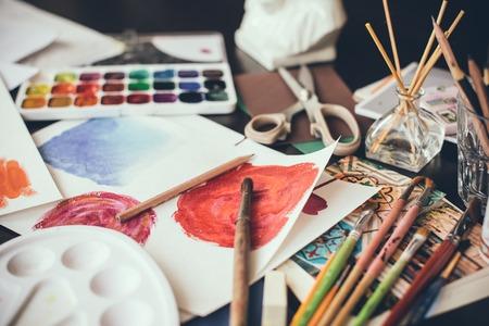 Mess In studio, colori ad acquerello, pennelli dell'artista e schizzi, palette e strumenti di pittura. Luogo di lavoro del progettista, stile vita bassa.