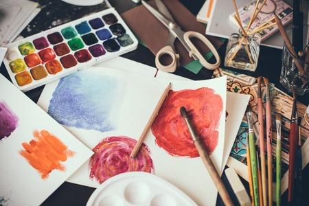 Puinhoop in het atelier van de kunstenaar, aquarel verf, penselen en schetsen, palet en tekengereedschappen. Werkplek ontwerper, hipster stijl.