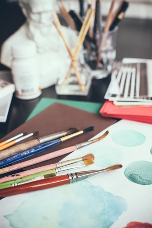artistas: Mess in the the artists studio, watercolor paints, brushes and sketches, palette and painting tools. Designers working place, hipster style. Foto de archivo