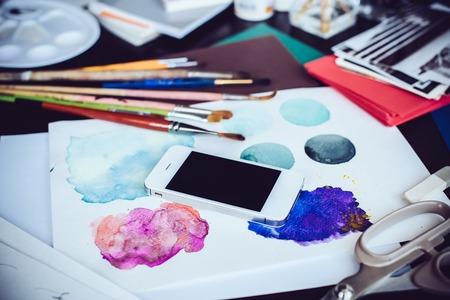 arte moderno: Smartphone en la mesa de estudio, las pinturas de acuarela, pinceles del artista y bocetos, paleta y herramientas de pintura. Arte y tecnología moderna, estilo inconformista. Foto de archivo