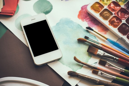 Smartphone on the table in the artists studio, watercolor paints, brushes and sketches, palette and painting tools. Arts and modern technology, hipster style.