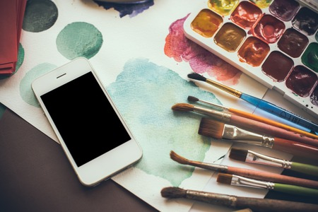 digital art: Smartphone on the table in the artists studio, watercolor paints, brushes and sketches, palette and painting tools. Arts and modern technology, hipster style.