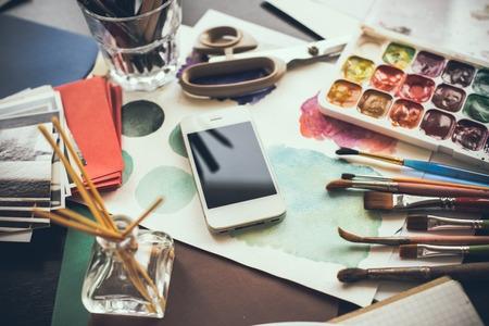 artistas: Smartphone en la mesa de estudio, las pinturas de acuarela, pinceles del artista y bocetos, paleta y herramientas de pintura. Arte y tecnología moderna, estilo inconformista. Foto de archivo