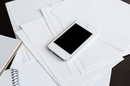 office space: Smartphone and clean empty white paper sheets on office table with copy space, business and communication