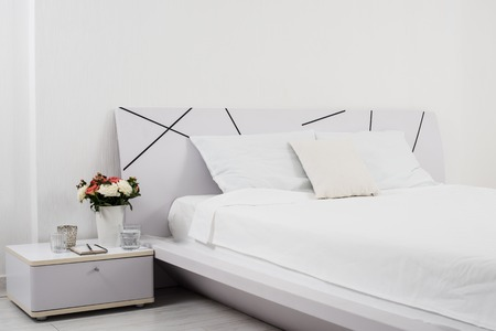 Interior of white bedroom, new linens on the bed in the hotel room Stockfoto