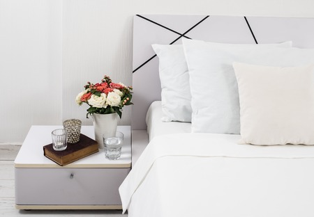 bedside: Interior of white bedroom, new linens on the bed, the room at the hotel. Bedside table decor and pillows closeup.