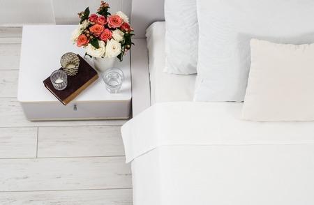 白い寝室、ベッドの上の新しいリネン、ホテルで部屋のインテリア。ベッドサイド テーブルの装飾と枕のクローズ アップ。