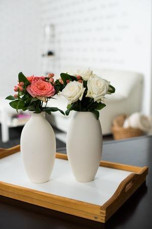 rosas blancas: Simple decoración interior de una casa, un jarrón de flores sobre una mesa en el interior del apartamento moderno