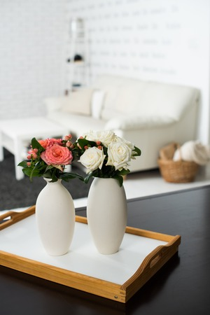 room decoration: Simple home interior decoration, vase of flowers on a table in the interior of modern apartment Stock Photo
