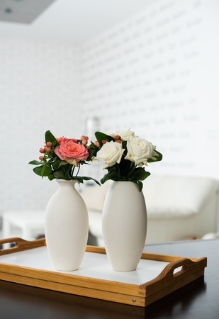 arrangements: Simple home interior decoration, vase of flowers on a table in the interior of modern apartment Stock Photo