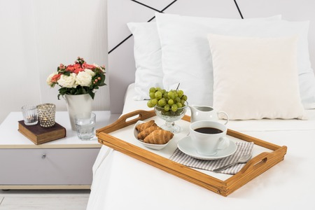 hotel room: Breakfast in bed, tray with coffee, fruits and croissants on a bed with white linen in bedroom interior, hotel room