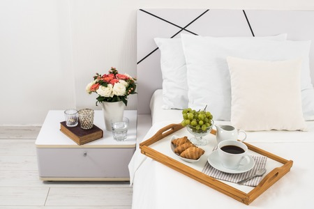 light breakfast: Breakfast in bed, tray with coffee, fruits and croissants on a bed with white linen in bedroom interior, hotel room