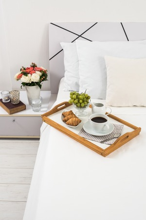 Frühstück im Bett, Tablett mit Kaffee, Obst und Croissants auf einem Bett mit weißer Bettwäsche im Schlafzimmer Interieur, Hotelzimmer